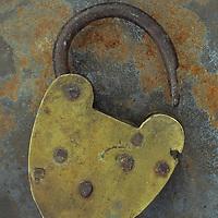 Old brass padlock lying on rusty metal sheet