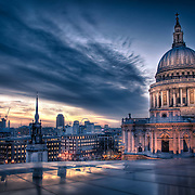 The view from the top of One New Change across to St. Paul's Cathedral in London as the sun sets, the sky turns a deep purple and the neon glow of the traffic and lights below illuminate the streets