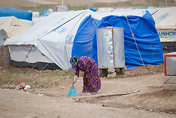© Licensed to London News Pictures. 12/05/2013. Dohuk, Iraq. A woman sweeps the ground outside her tent at a refugee camp for Syrian refugees in Iraqi-Kurdistan. The camp, close to the city of Dohuk, now houses in the region of 45,000 refugees, with around 400 new arrivals every day. Photo credit: Matt Cetti-Roberts/LNP