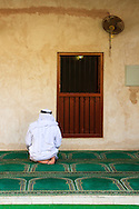 Muslim man praying at the traditional mosque in the Abu Dhabi Heritage Village.