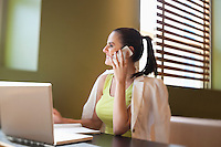 Happy young woman sitting at desk with laptop using cell phone