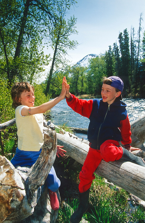 Alaska. Kenai Peninsula. Seven year old twins Alex and Marina Graham high five on a summer day near the Russian River. MR.
