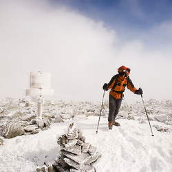 Man winter hiking.  Rime ice covers the rocks and a trail sign on Mount Washington in New Hampshire's White Mountains.  Nelson Crag Trail.  March.
