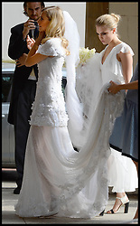 Cara Delevingne holds her sisters poppy dress as they arrive at  Poppy's wedding to James Cook at St.Paul's Church in Knightsbridge, London,  Friday, 16th May 2014. Picture by Stephen Lock / i-Images