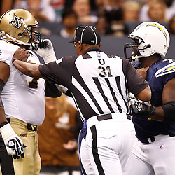 August 27, 2010; New Orleans, LA, USA; umpire Chad Brown (31) separates New Orleans Saints guard Jahri Evans (73) and San Diego Chargers defensive end Derrick Jones (77) during the first half of a preseason game at the Louisiana Superdome. The New Orleans Saints defeated the San Diego Chargers 36-21. Mandatory Credit: Derick E. Hingle