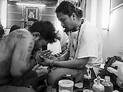 "07 MARCH 2015 - NAKHON CHAI SI, NAKHON PATHOM, THAILAND: A man who got a spiritual Sak Yant tattoo (left) prays with the tattoo master at the Wat Bang Phra tattoo festival. Wat Bang Phra is the best known ""Sak Yant"" tattoo temple in Thailand. It's located in Nakhon Pathom province, about 40 miles from Bangkok. The tattoos are given with hollow stainless steel needles and are thought to possess magical powers of protection. The tattoos, which are given by Buddhist monks, are popular with soldiers, policeman and gangsters, people who generally live in harm's way. The tattoo must be activated to remain powerful and the annual Wai Khru Ceremony (tattoo festival) at the temple draws thousands of devotees who come to the temple to activate or renew the tattoos. People go into trance like states and then assume the personality of their tattoo, so people with tiger tattoos assume the personality of a tiger, people with monkey tattoos take on the personality of a monkey and so on. In recent years the tattoo festival has become popular with tourists who make the trip to Nakorn Pathom province to see a side of ""exotic"" Thailand.   PHOTO BY JACK KURTZ"
