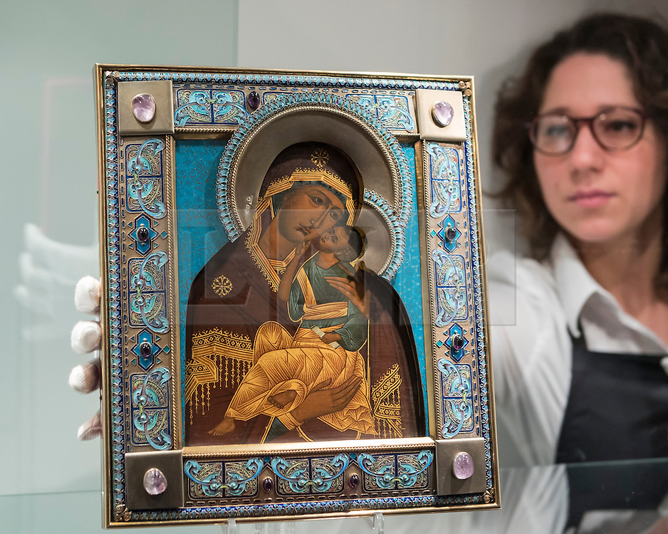 """© Licensed to London News Pictures. 25/11/2016. London, UK. A technician examines """"A Fabergé gem-set silver-gilt and enamel icon of the Yaroslavskaya Mother of God"""" (est. GBP 30-50k), at the preview of artworks from Sotheby's upcoming Russian sales in New Bond Street, where over three hundred works spanning several centuries will be offered. Photo credit : Stephen Chung/LNP"""
