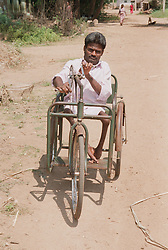 Indian man affected by polio; member of selfhelp group supported by charity ADD India; riding adapted tricycle using hands,