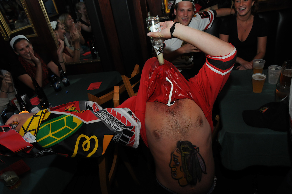 "Matt Pearlman, 25 (bottom) performs a ""beer monster"" to celebrate a Chicago Blackhawks goal scored against the Philadelphia Flyers during a Stanley Cup Finals viewing party at Mahoney's Pub. Pearlman created the celebratory tradition for the occasion of a Blackhawks goal and as a way to pump himself and friends up before games begin."