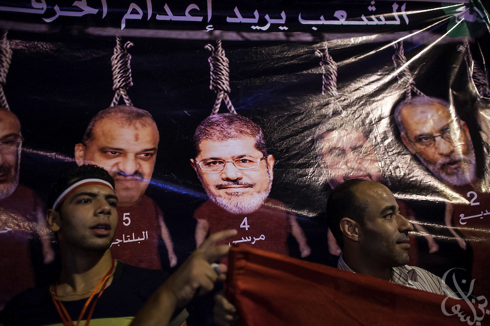 "Egyptians hold a sign calling for the hanging of the leaders of the Muslim Brotherhood political party including (c) deposed President Mohamed Morsi during take mass demonstrations called for by Gen. Abdel Fattah El Sissi, the head of Egypt's military, in the Tahrir Square area of downtown Cairo Egypt on Friday July 26, 2013. EL Sissi had asked Egyptians to take to the streets on Friday to show the world that he had a mandate to deal with ""violence and terrorism""."