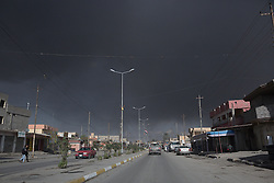 Licensed to London News Pictures. 02/11/2016. Qayyarah, Iraq. A thick smoke cloud, coming from nearby burning oil wells which were set alight by retreating Islamic State militants, covers the sky over the main street through the Iraqi town of Qayyarah.<br /> <br /> Two months after being liberated from the Islamic State, the Iraqi town of Qayyarah, located around 30km south of Mosul, is still dealing with the environmental repercussions of their ISIS occupation. The town's estimated 15,000 inhabitants constantly live under, and in, heavy clouds of smoke which often envelope the settlement. The clouds emanate from burning oil wells in a nearby oil field that were set alight by retreating ISIS extremists after a two year occupation. The proximity of the fires, often right next to homes within the town, covers many buildings and residents with thick soot and will lead to long term health and environmental implications. Photo credit: Matt Cetti-Roberts/LNP