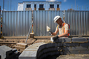 A builder uses a trowel and a spirit level to lay the first bricks with cement onto the foundations of a new house on a home building construction site in Norwich. Norfolk. United Kingdom  (photo by Andrew Aitchison / In pictures via Getty Images)