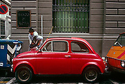 In a narrow street in Florence, a parking attendant stops to check the windscreen (windshield) of a Fiat 500 car. Squeezed into a space that only a car of this length can occupy, the lady warden bends to inspect the owner's city permit. Traffic police in Florence issue approximately 90 tickets every minute, 1,253 tickets a day so a motorist in Florence receives a traffic violation every 40 seconds, according to official figures. Ticket fines average about 140 euro per motorist bringing about 52 million to city hall each year, making it one of Italy's most heaviest fined cities. Officials note that the money entering the municipal budget through traffic fines has tripled in the last 10 years. The Fiat 500 (Cinquecento) designed by Dante Giacosa was produced by Fiat between 1957 and 1975.