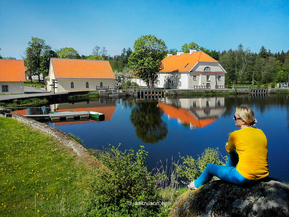 Woman siiting on stone in Vihula manor. Estonia, old buildings reflecting on water.