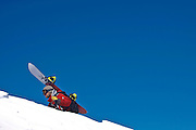 SHOT 3/12/10 11:13:29 AM - A guide works his way up the ridgeline at Silverton Mountain in Silverton, Co. while leading a group of skiiers and snowboarders. Skiing and snowboarding at Silverton Mountain in Silverton, Co. Silverton Mountain is unique amongst ski resorts requiring a guide (most of the season), avalanche gear and limiting the number of daily visitors. There are multiple bowls, chutes, cliffs and natural terrain features to be discovered during a visit to Silverton Mountain. It is the highest Ski Area in North America with a peak of 13,487' and it is also the steepest with no easy way down. The mountain is left in it's natural state with the exception of the avalanche reduction work which occurs. There is only one chair at the mountain though most skiiers and snowboarders will end up hiking in various directions at the top. The mountain also features heliskiing trips for $159 a trip (at the time of visit). The mountain opened in 2002. (Photo by Marc Piscotty / © 2010)