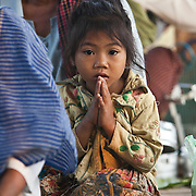 A young Cambodia girl offers prayers during a simple Buddhist blessing ceremony near Pailin, Cambodia, along the border with Thailand.