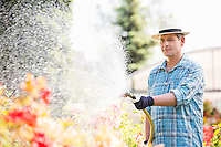 Man watering plants outside greenhouse