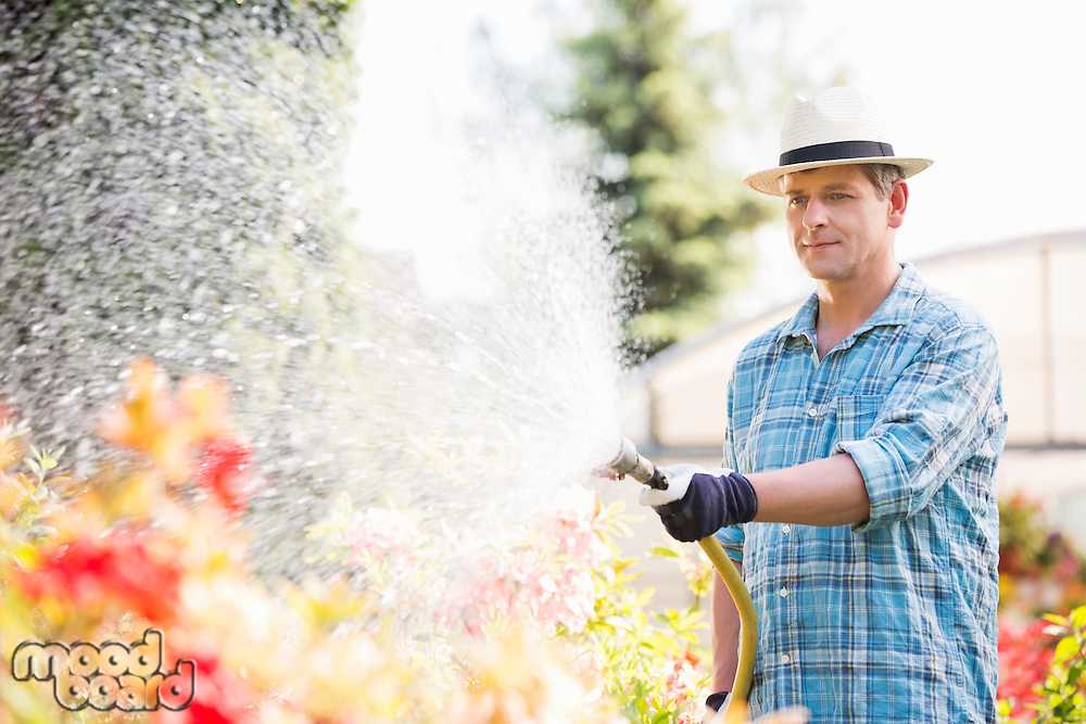 Man watering plants outside greenhouse