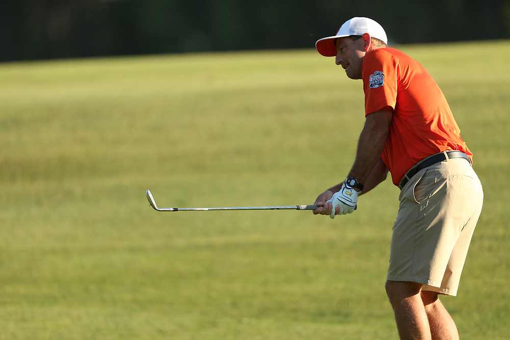 Clemson  head football coach Dabo Swinney chips the shot during the Chick-fil-A Peach Bowl Challenge at the Ritz Carlton Reynolds, Lake Oconee, on Tuesday, April 30, 2019, in Greensboro, GA. (Chris Collins via Abell Images for Chick-fil-A Peach Bowl Challenge)