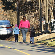 A women with two children walks down the street near the school in Sandy Hook after today's shootings at Sandy Hook Elementary School, Newtown, Connecticut, USA. 14th December 2012. Photo Tim Clayton