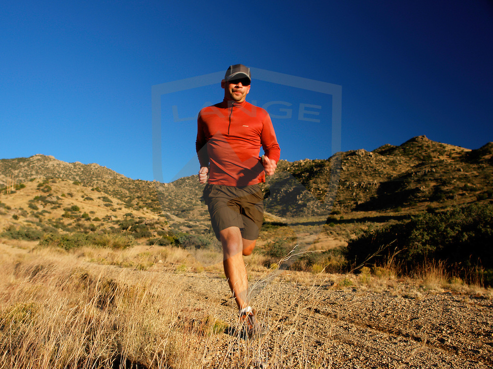 outdoor sports and recreation and nature scenery: male (man) trail runner in stride with red shirt, cap, and sunglasses trail running at sunset in the sandia mountains of albuquerque, new mexico, usa,