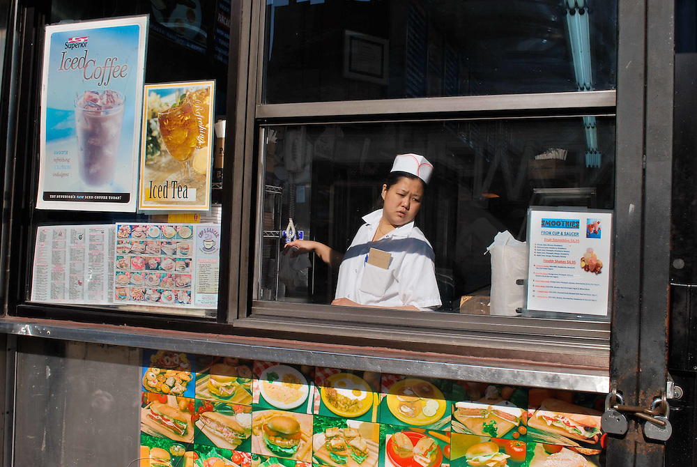 A woman seen working through the window of a Chinese diner in Chinatown, New York