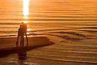 The boat launch at Point Holmes and sunset colors enhance the romantic mood of this silhouetted couple.  Point Holmes, Comox Valley, Vancouver Island, British Columbia, Canada