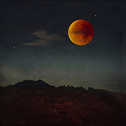 Photomanipulation - bllod moon over a rocky nightly landscape. <br />