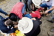 Goshen, Conn. - June 21, 2009 - Evaldo Silva is comforted by fellow rodeo riders after he broke his leg riding a bull during Sunday's rodeo in the 4th annual Goshen Stampede..Josalee Thrift Photo