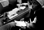 An East African immigrant and her son receive a housing voucher for a couple of nights stay at a motel from a staff member of the ROAR (Referals, Opportunities, Advocacy and Resources) of Washington..