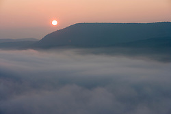 The sun rises above fog on the Connecticut River as seen from South Sugarloaf Mountain in the Sugarloaf Mountain State Reservation in Deerfield, Massachusetts.