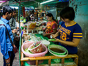28 MAY 2018 - BANGKOK, THAILAND: Women from Myanmar makes of betel to sell to Burmese people in Phra Khanong Market in Bangkok. The market serves a mix of Thai working class people and immigrants from Myanmar (Burma). Betel used to be popular in Thailand but was banned in the 1940s and now only a few older Thais still chew the mild stimulant. It's still very popular in Myanmar and it's not unusual to find market stalls selling betel in Burmese migrant communities in Thailand.      PHOTO BY JACK KURTZ