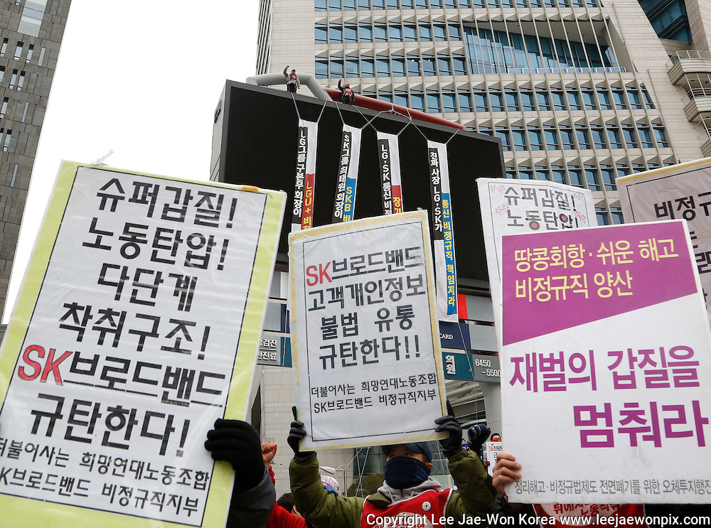 Two non-regular workers (top C) of subcontractors of LG Uplus and SK Broadband, who have been holding a sit-in on an advertising tower to demand working hour reduction and wage increase since February 6, 2015, chant slogans as other protesters march after a rally demanding resignation of South Korean President Park Geun-hye in central Seoul February 28, 2015. About 3,000 protesters attended the rally. The two workers also demand the two companies to make non-regular workers permanent. (Photo by Lee Jae-Won)<br />