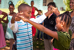 Housani Joseph, left, dances with Deshyla Joseph for visiting Dancing Classrooms Global Program Director Rodney Lopez., demonstrating what they've learned over the course of ten weeks and twenty lessons.  Claude O. Markoe Elementary School Dancing Classrooms VI Culminating Event.  17 December 2015.  Christiansted, St. Croix.   © Aisha-Zakiya Boyd.and One twins.  © Aisha-Zakiya Boyd