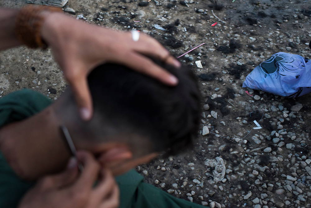 Ahmad, an Iraqi Kurd, gets a haircut at a refugee camp on the Macedonian (FYROM) border on March 8, 2016 in Idomeni, Greece. Several enterprising refugees have set up services such as haircuts, which cost 2 Euros each.