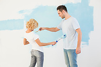 Playful couple painting each other in new house