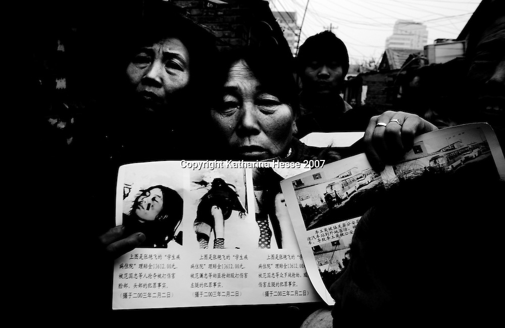 BEIJING, DECEMBER-22:  2 petitioners hold law cases from the countryside... In the past decades, hundreds of thousands of Chinese from the provinces have descended upon Beijing in hopes of attracting attention from higher authorities regarding their civil law cases. These cases vary from work accidents, violence against family members, murder, extortion, and the majority of which stem from a corrupt rural legal system...The tradition of petitioning to higher authorities in the Chinese capital reaches back to Imperial times. Outside the city center of Beijing, petitioners' villages sprung up as those seeking justice face long delays in being heard. The petitioners today face tremendous obstacles in having their cases heard; authorities are overworked due to the sheer number of complaints, which are often clumsily presented without aid of a legal adviser. In addition, Provincial as well as undercover police try to stop the petitioners from going to the National Petition offices to file their cases. If caught, they are briefly sent to an unofficial detention centre where they are held and forced to take the train back to the provinces. For many of the petitioners, it has become their life mission to make the regular journey to the capital only to be sent back without ever having been heard...The number of petitioner villages has been reduced significantly as the preparations for the 2008 Olympics progress. Many fear these villages will be gone by the summer of 2008..