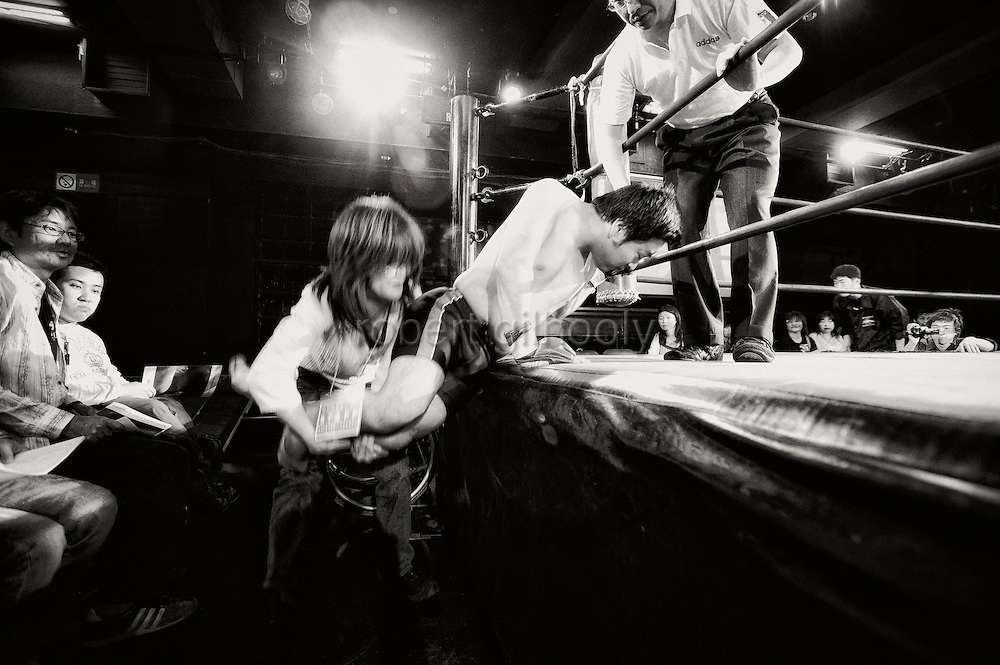A wrestler gets a helping hand into the ring prior to a bout at Doglegs, an event for wrestlers with physical and mental challenges in Tokyo, Japan.