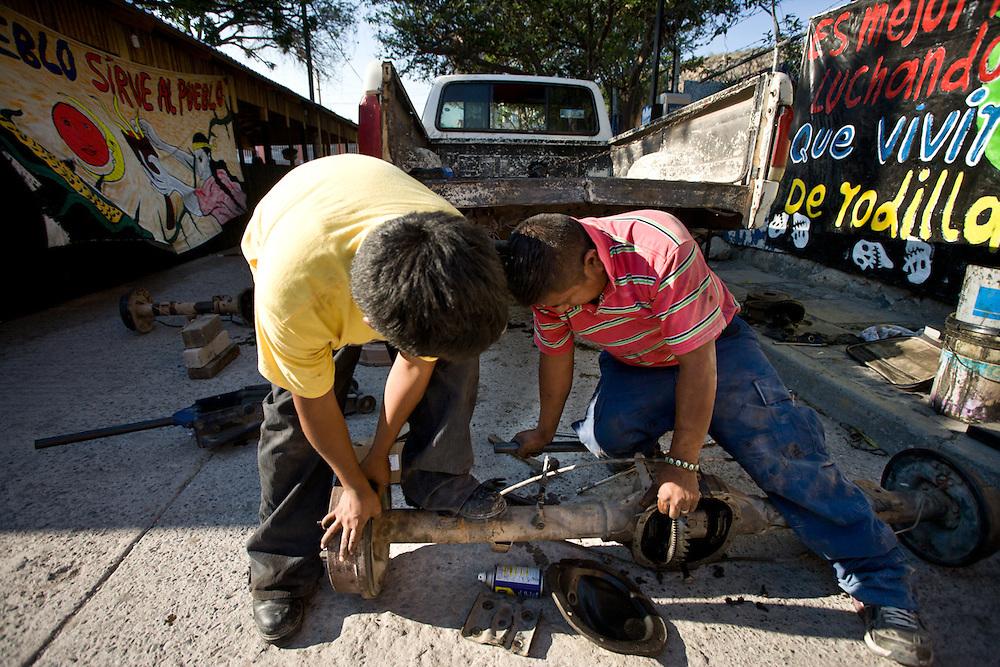 Adrian Salvador and Flavio Aquino Hidalgo fix a community police car. They also both volunteer in the community police.