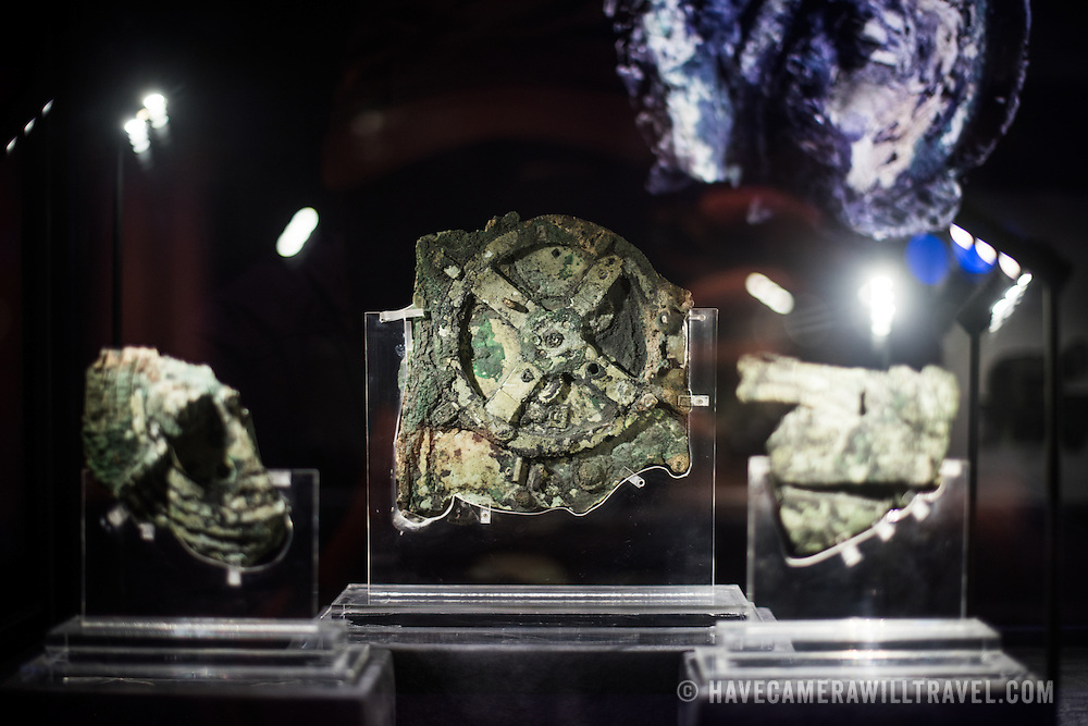 One of the highlights of the National Archaeological Museum in Athens, Greece, the Antikythera Mechanism now has its own dedicated exhibit gallery in which all of its fragments are on display. Believed to date to somewhere around 100 BC to 205 BC, it was found amongst a large cache of statues, coins, and other artefacts on a sunken shipwreck discovered in 1900 by sponge divers off the coast of the Greek island of Antikythera. It was badly damaged after such a long time in the salt water, but extensive research in recent decades has resulted in a consensus that it is a kind of astronomical analog computer as well as some modern reconstructions. In the center is the largest piece, with the circular gear clearly visible, that is known as Fragment A. it contains most of the Mechanism's gears.
