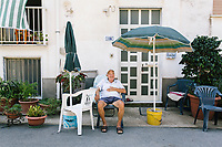 ACCIAROLI, ITALY - 14 SEPTEMBER 2018: Edmund (81) sits here in front of his house everyday in Acciaroli, a small fishing village in the municipality of Pollica, Italy, on September 14th 2018.<br /> <br /> To understand how people can live longer throughout the world, researchers at University of California, San Diego School of Medicine have teamed up with colleagues at University of Rome La Sapienza to study a group of 300 citizens, all over 100 years old, living in Acciaroli (Pollica), a remote Italian village nestled between the ocean and mountains in Cilento, southern Italy.<br /> <br /> About 1-in-60 of the area's inhabitants are older than 90, according to the researchers. Such a concentration rivals that of other so-called blue zones, like Sardinia and Okinawa, which have unusually large percentages of very old people. In the 2010 census, about 1-in-163 Americans were 90 or older.