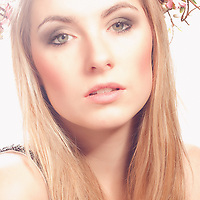 Young woman with flowers in her blonde hair facing the camera