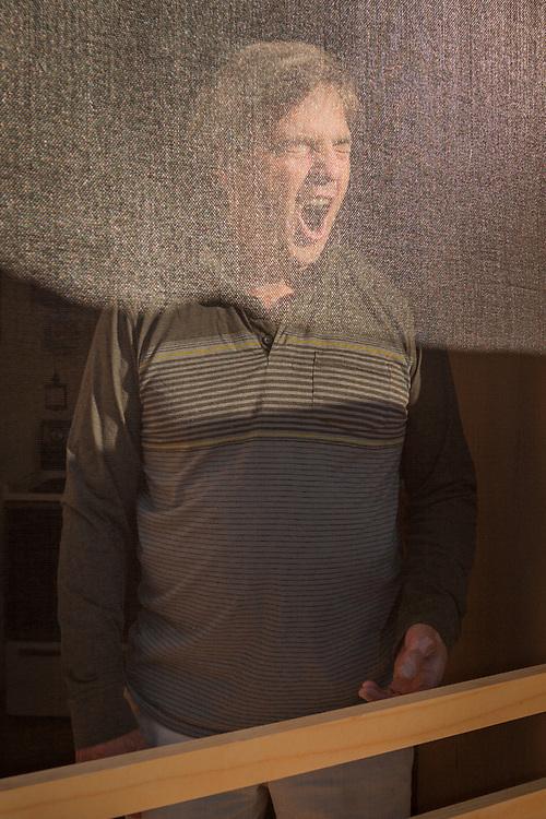 David Freeman greets the morning from behind the screen door of his cabin in the Kenai Keys subdivision on the Kenai River near Soldotna, Alaska.