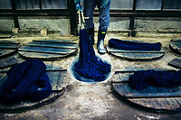 A man beats indigo dye into strands of cotton at the Yamamura workshop in Kyushu, Japan.