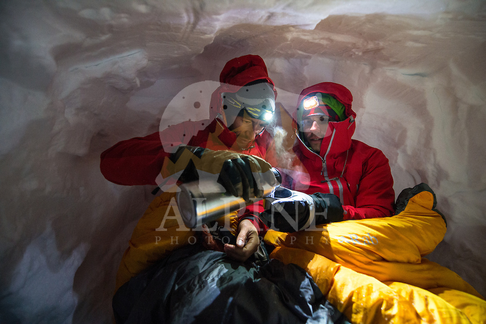 A male mountaineer covered with a sleeping bag pours a warm tea for his fellow in an improvised snow cave on Glacier Blanche, Chamonix, France.