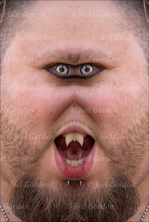 Fantasy portrait of male with fangs, face piercing and color contact lens.