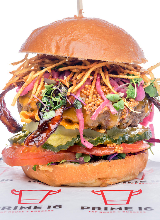 "Photo by Mara Lavitt<br /> New Haven, CT<br /> March 27, 2017<br /> Prime 16 (New Haven location) burgers. <br /> Prime 16 ""Elm City Crunch"": Prime 16 signature beef patty, sriracha-glazed bacon, Wisconsin cheddar cheese, potato straws, pickled mustard seed, dill pickles, white onion, sliced tomato, and micro greens, all on a brioche bun."
