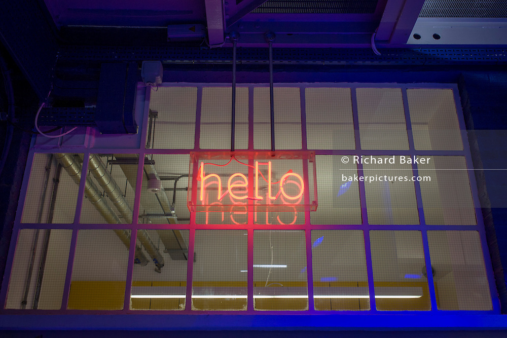 A neon Hello sign in the window of a corporate office entrance in central London.