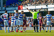 Referee Andrew Madley tries to keep Queens Park Rangers and Swansea City players at bay during the EFL Sky Bet Championship match between Queens Park Rangers and Swansea City at the Loftus Road Stadium, London, England on 13 April 2019.
