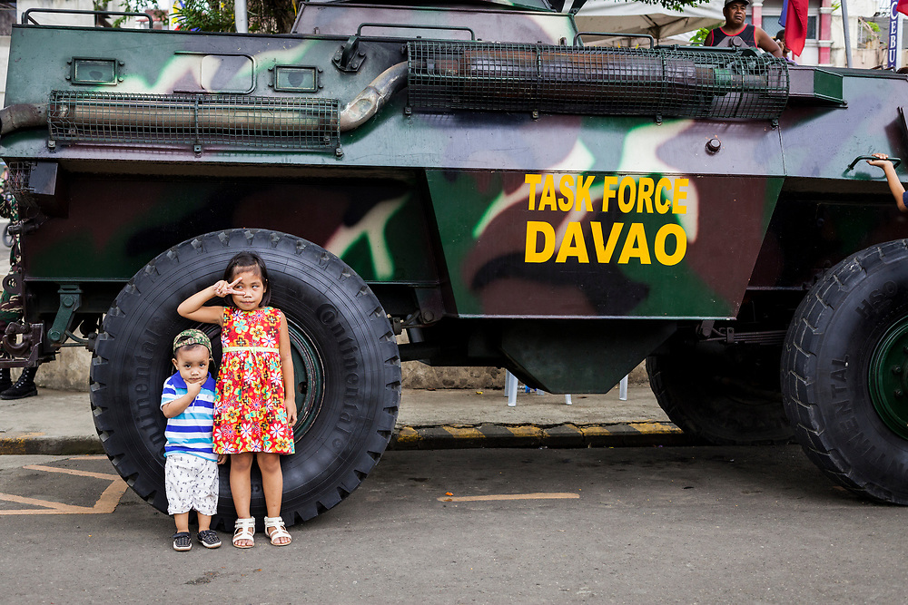 Davao City, Mindanao, Philippines - JUNE 18: A boy and a girl are seen posing in front of the Davao Task Force Army tank that stands by at Quezon Park near Davao City Hall.  Security in the city is tight since President Duterte implemented a Martial Law for 60 days in Mindanao due to the heavy fighting in Malawi 250km away.